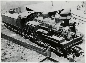 View looking down on Shay train engine.  Man standing on engine.