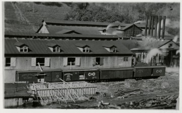 Front view of a mill and stacks.  C&O train cars in front.