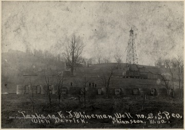 Men stand atop oil tanks with derrick in the background.