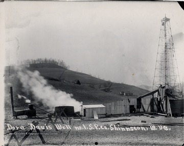 Oil derrick and adjoining oil company buildings.