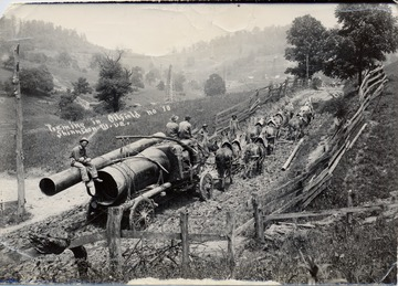 Team of eight horses pulling oil equipment up a muddy hill.