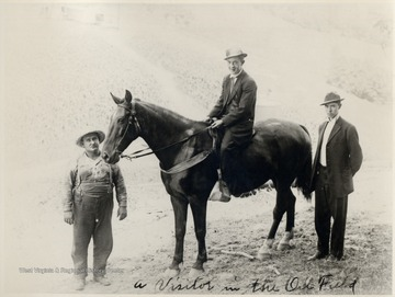 Man on a horse with two men standing beside the horse.
