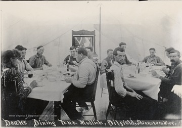 People sitting down at two tables eating a meal.
