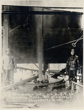 Oil flows into the air between two oil workers.