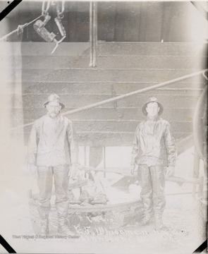 Two men standing beside an oil well.