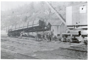 Crane and crew members putting a railroad car back on the track.