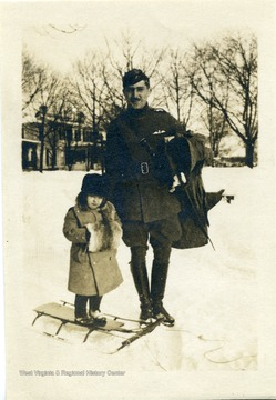 Candid portrait of Lt. Louis Bennett in uniform posing with a small child on a sled.