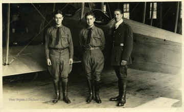 "Officers of the West Virginia Flying Corps, including (left to right) Lieutenant Thomas Kent, Captain Louis Bennett, Jr., and Lieutenant William Frey.  They are standing in front of a Curtiss JN or ""Jenny"" aircraft.  This photograph appeared with an article regarding the W. Va. Flying Corps in the July 29, 1917 issue of the Wheeling Sunday News on page eight of part iii."