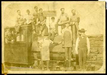 Group portrait of the Marilla Window Glass Cutters of Morgantown, W. Va. On Engine from left to right: Arthur Lewis, Hugh Fairfield, Dan McLamell, Jim Kifer, Deney Lelabey, Fred Salzman, Orcan DuBoise, Frank Dallons. Standing on Engine: Harry Davenport. Standing on platform: Arthur Swan, Bill Lewis.