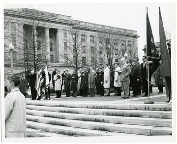 A group of men salute the American flag at a ceremony honoring World War II veterans and the U.S.S. West Virginia battleship.