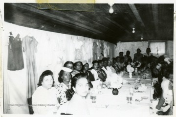 Candid group portrait of African-American Extension workers at the Filbert Achievement Day Exhibit and Luncheon. Many women are sitting at a large table with dresses hanging on the walls behind them.