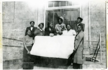 Group portrait of female African-American Extension workers holding a flag in front of a building.