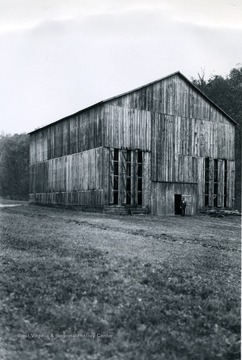 Exterior view of the tobacco barn constructed by Mr. A. C. Curry in Lincoln County. 'Narrow Ventilation doors which were opened in the front of the barn for this picture are located on all four sides of the barn. The barn is 50 feet wide, 60 feet long and 41 feet to the roof at the center of the barn.'