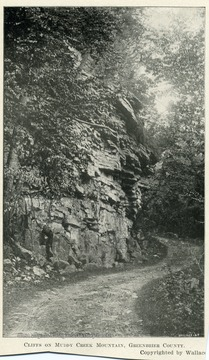A winding mountain road towered over by rocky ridges. Copyrighted by Wallace.