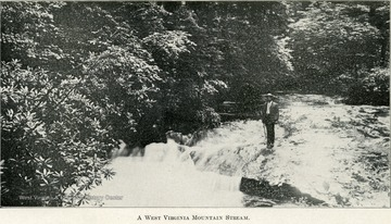 A man stands on a rock that juts out into the side of a stream.