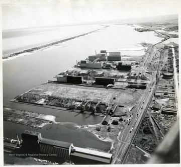 Consolidated elevators in foreground; Docks #1, Pgh Coal Co. 'abandoned'; Docks #7 'used section'; Docks #7 'abandoned section'; Consolidated Elevators; Cleveland Cliffs Coal Docks; Capitol Elevators; North Western Fuel Co. Coal Docks #4 'Consolidated Coal Co.'; Occident Elevators; Planey Elevators; Long strip of land is Minnesota and Wisconsin Points separating the harbor from Lake Superior. Photographed in fall 1942.