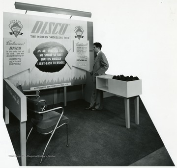 A man stands next to the Disco Fuel exhibit.