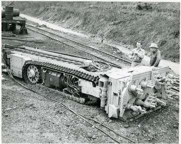 Two men standing next to a continuous mining machine.