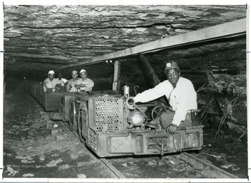 Julius Blaney driving a coal cart with people in a coal mine.