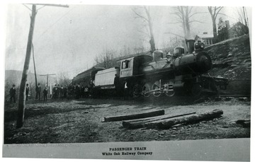 Passenger Train of White Oak Railway Co. with a line of people outside of it.