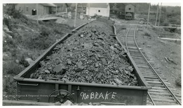 View of three coal cars. First coal car has 'No BRAKE' written on it.