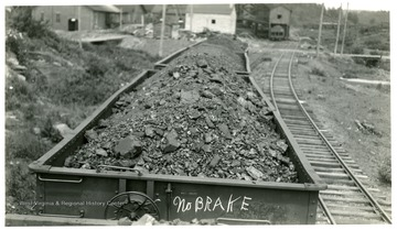 Loaded coal cars.  First car has 'No BRAKE' written on it.