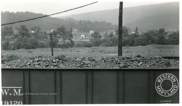 Filled Coal car with houses in background.
