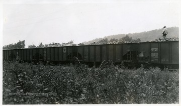 A man walking along top of coal cars.
