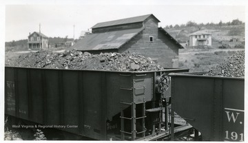 Coal cars with a barn and houses in the background.