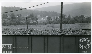 Filled coal car with houses visible in the background.