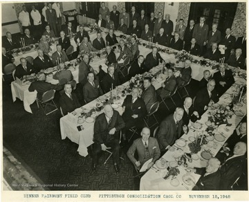 Lewis is seated at the table on the right.