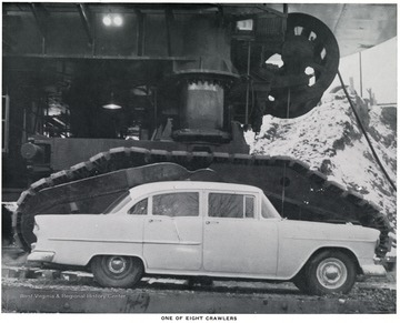 A car parked next to the Mountaineer crawler to demonstrate size.  Hanna Coal Company, Division of Pittsburgh Consolidation Coal Company.