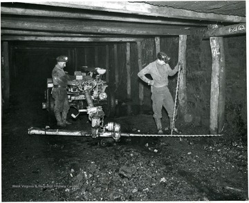 Two men using large bits to drill prior to placing charges.