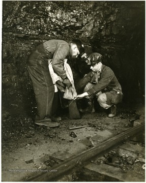 Two miners take samples of coal.