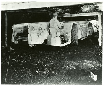A miner operates an electric shuttle car in the mine.