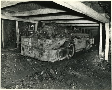 A miner moves a fully loaded shuttle car down the mine shaft.