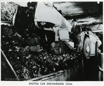 A miner empties his shuttle car.