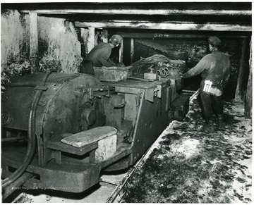 Two miners operate a track mounted coal cutting machine.