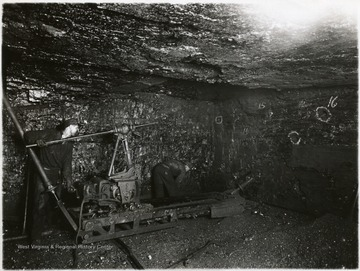 Two miners operate the breast type coal cutting machine.