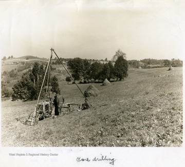 Men work with core drilling equipment on a hillside.