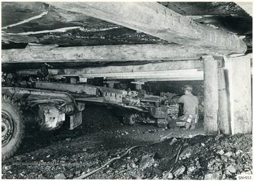 A miner operating a coal cutting machine.