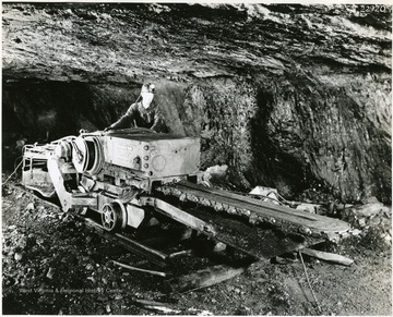 Miner on a small, track mounted, cutting machine.