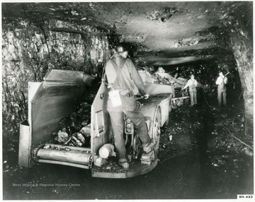 Miners at work with loading machine and shuttle car.