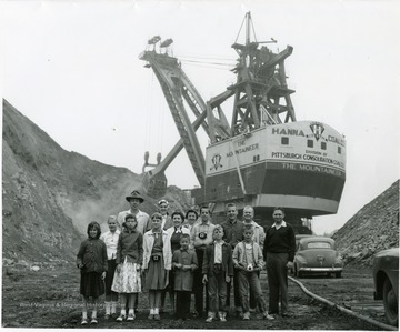 Group portrait of children standing in front of the large shovel 'The Mountaineer'.