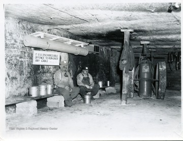 Two men sitting on a bench in a mine in an underground mine.  Sign reads, 'It is a dischargeable offence to run over any cable.'