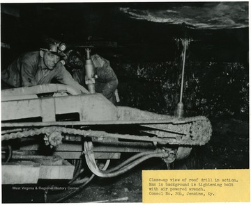 Close-up view of roof drill in action. Man in background is tightening bolt with air powered wrench at Consol. No. 204, Jenkins, Ky.