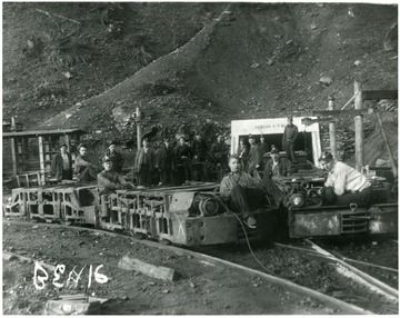 Miners on cars in front of the entrance to the Bergoo No. 3 Mine. Rear Left to Right:  Ernest 'Windy' Rose, Argil Rose (on car), Oliver Williams, French Dunlop, Ernie Riffle (later killed in a mine accident at the same mines), Mike Hamilton, Hartsel Friend, Lloyd Crites, Fred Bennett?, Russell Heaveners; Motor Men: Bucky Rexroad (left) and Okey Grien (right), Gordon Ward (2nd motor left) and Gillepsie (2nd motor right), Hick Hardway (standing on car), Ray Riffle (leaning on car).
