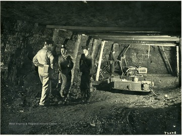 Miners talking while others run drilling equipment.