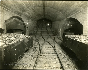 Coal carts on tracks and corridor openings in an underground mine in Monongalia County.