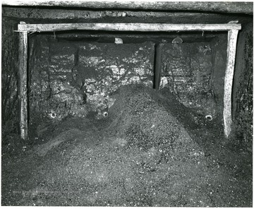 Notice the preparatory cut and the 3 charge-holes near floor of the mine.